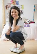 Smiling mixed race teenage girl crouching on scale Stock Photos