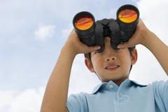 mixed race boy looking through binoculars - stock photo