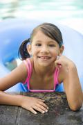 smiling mixed race girl leaning on edge of swimming pool - stock photo