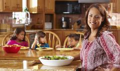Mother serving salad to children Stock Photos