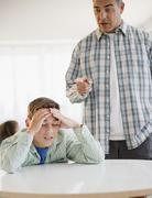 hispanic father lecturing frustrated son - stock photo
