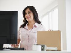 Smiling hispanic woman with cardboard box using computer Stock Photos