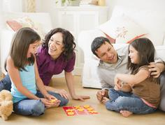 Father and mother playing game in livingroom with children Stock Photos