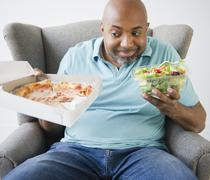 African american deciding between salad and pizza Stock Photos