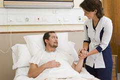 Nurse comforting patient in hospital room Stock Photos