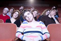Valkoihoinen nainen katsomassa elokuvaa teatterissa Kuvituskuvat