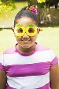 Smiling hispanic girl wearing pineapple sunglasses Stock Photos