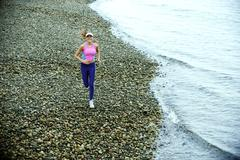 Valkoihoinen nainen käynnissä Pebble Beach Kuvituskuvat