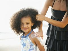 Hispanic mother rubbing sunscreen on daughter at beach Stock Photos