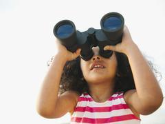 Mixed race girl looking through binoculars Stock Photos