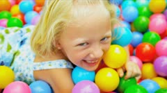 Laughing Little Girl Playing Plastic Balls Stock Footage