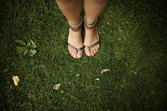 Hispanic woman wearing anklets and sandals Stock Photos