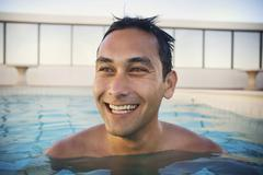 Mixed race man swimming in swimming pool Stock Photos