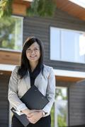 mixed race real estate agent standing near house - stock photo