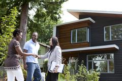 Real estate agent greeting couple at house Stock Photos