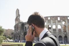 Italialainen liikemies puhuu matkapuhelimeen ulkona Kuvituskuvat