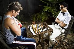 Geek and body builder playing chess Stock Photos