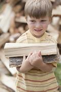 Caucasian boy carrying firewood Stock Photos