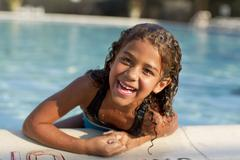 Mixed race girl swimming in swimming pool Stock Photos