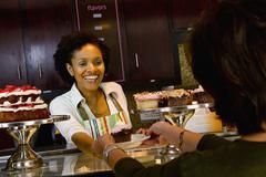 African american bakery owner serving customer cupcake Stock Photos