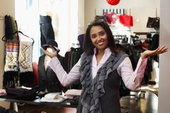 Mixed race small business owner standing in clothing shop Stock Photos