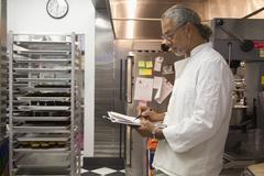 African american small business owner working in bakery kitchen Stock Photos
