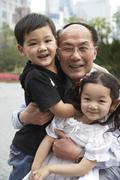 chinese grandfather and grandchildren smiling - stock photo