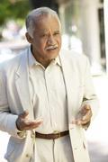 Uncertain hispanic man standing outdoors Stock Photos