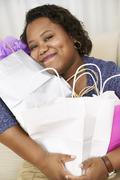 Afrikkalainen amerikkalainen nainen halaa ostoskassit Kuvituskuvat