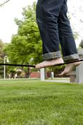 Caucasian man balancing on rope in park Stock Photos