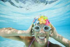 Hispanic woman in retro swimming cap underwater in swimming pool Stock Photos