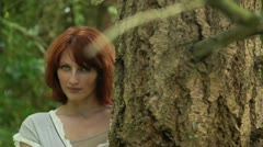 Stock Video Footage of pretty redhead woman standing by a tree