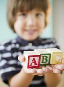 Hispanic boy holding alphabet blocks Stock Photos