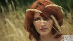 Stock Video Footage of pretty redhead woman sitting in a grassy field