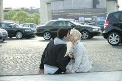 Caucasian man kissing girlfriend on busy street Stock Photos