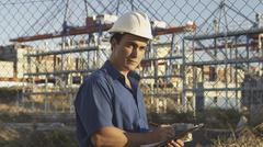 hispanic man with clipboard on construction site - stock photo
