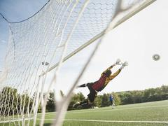 Mixed race goalkeeper in mid-air protecting goal Stock Photos