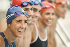 Smiling hispanic swimmers standing in a row Stock Photos