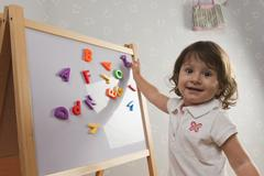 Hispanic baby playing with letters on magnetic board Stock Photos