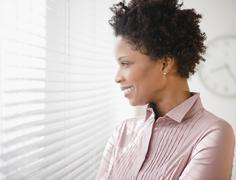 Black businesswoman looking out window Stock Photos
