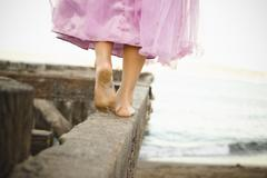 Mixed race girl in costume walking on dilapidated pier Stock Photos