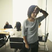 Businesswoman leaning wall with co-workers in background Stock Photos