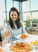 Woman serving pasta at table Stock Photos