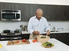 Black man preparing salad in kitchen Stock Photos