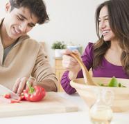 Couple preparing salad together Stock Photos