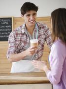 Man serving woman coffee to go Stock Photos