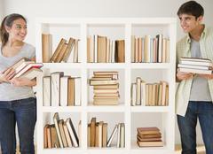 Couple with books standing near bookshelf Stock Photos