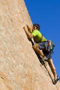Latinalaisamerikkalainen mies kalliokiipeilyä Kuvituskuvat