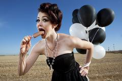 Glamorous woman holding balloons and eating popsicle Stock Photos
