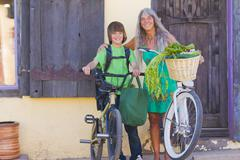 Caucasian grandmother and grandson standing with bicycles Stock Photos